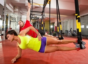20110952-crossfit-fitness-trx-training-exercises-at-gym-woman-and-man-side-push-up-workout